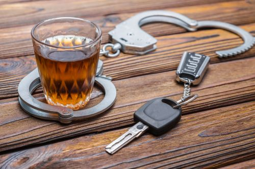dui image: handcuffs around an alcoholic drink and car keys