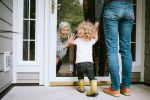 Little Girl Visits Grandparents Through glass door